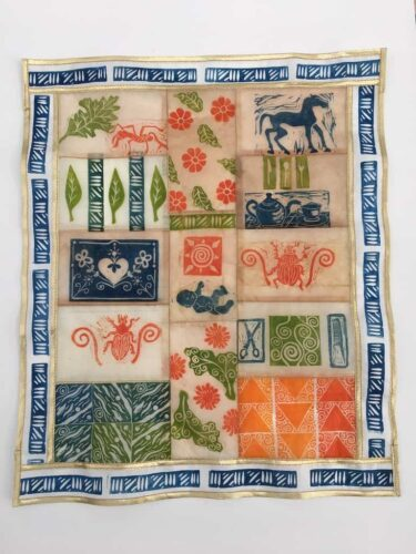 Hand carved stamps printed on tea bags, and are sewn together to create a mini- quilt.